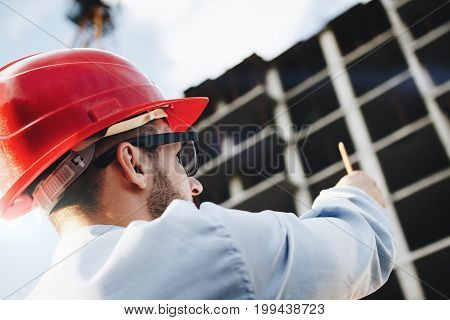 Young Bearded Engineer Or Architect In Red Hard Hat With Pencil In Hand At Construction Site. Busine