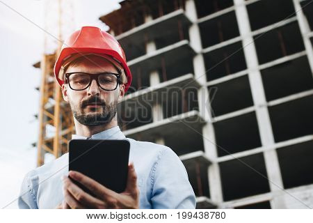 Engineer Or Architect In Helmet With Tablet In Hand On Construction Site. Modern Builder Engineer In