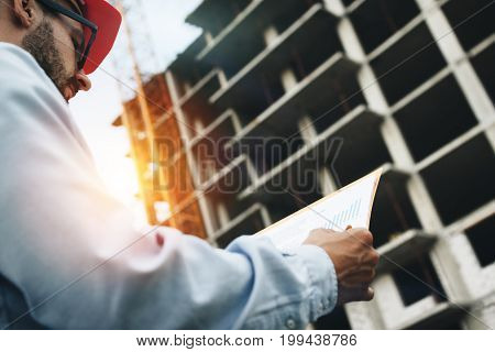 Close Up Portrait Engineer Or Architect Working On A Building Site And Holding Blueprints. Engineeri