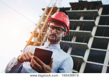 Modern Construction Engineer Or Architect In Helmet At Construction Site Works With Industrial Elect