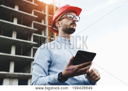 Modern Engineer Or Architect Works On Construction Site With Electronic Tablet. Young Man Builder Wi