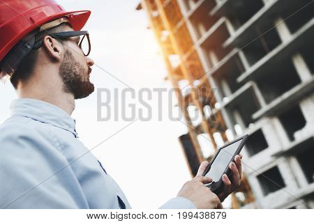Young Bearded Businessman Builder With Modern Electronic Tablet On Construction Site. Architect Look