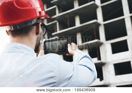 Young Construction Engineer In Helmet Checks Project Of Building On Electronic Tablet. Modern Builde