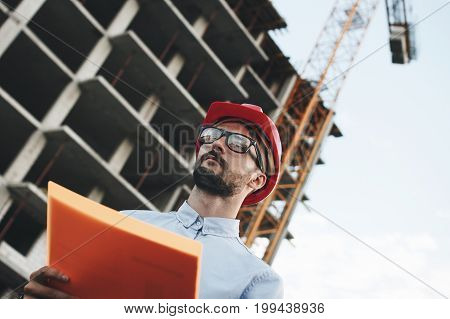 Young Modern Engineer Builder Or Architect With Folder Of Documents On Background Of Building Being