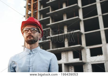 Portrait Of Modern Civil Engineer On Background Of Building Construction