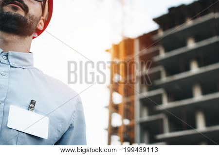 Blank White Badge Or Business Card On Chest Of A Shirt Of  Modern Engineer Or Architect In A Red Har