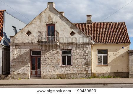 Old stone dwelling with tile roof along the street. Typical Northern Europe town architecture.
