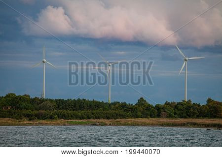 Wind power generators on the coast of Baltic sea. Summer cloudy wheather.