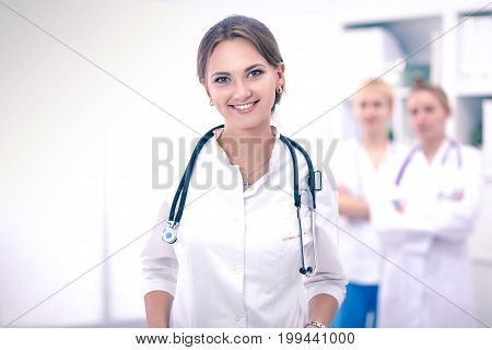 Young woman doctor standing at hospital with medical stethoscope.