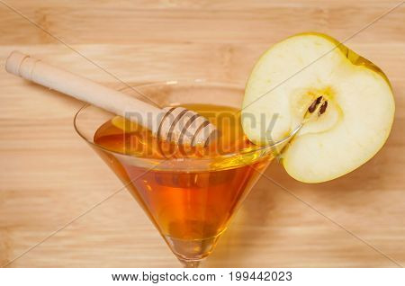 Honey stick in the pure honey inside of a martini glass decorated with an apple slice. Rosh Hashanah (Jewish New Year) greeting card illustration. Shana tova, have a sweet New Year wish card.