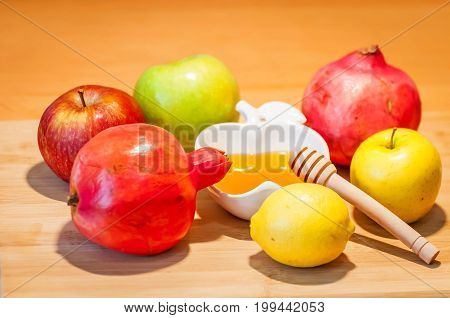 Beautiful green, yellow and red apples, pomegranates and lemons with honey on a wooden background. The traditional Jewish holiday Rosh HaShanah (Jewish New Year) concept.