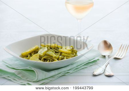 Linguine pasta with pesto genovese and potatoes over a table with cutlery and white wine glass