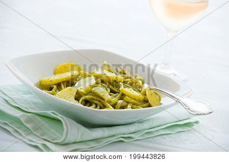 Linguine pasta with pesto genovese and potatoes over a table with fork and white wine glass
