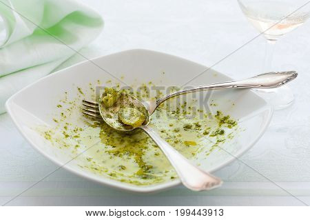 Closeup of eaten linguine pasta plate with pesto genovese potatoes and white wine glass