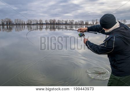 Fisherman in action. Man playing fish by fishing rod