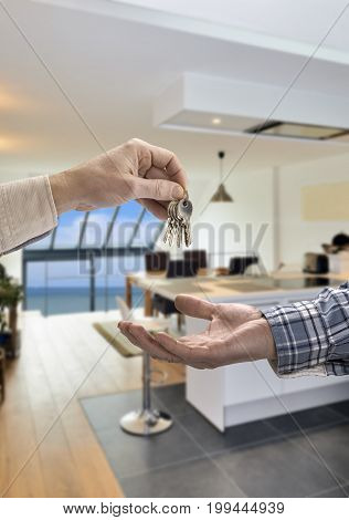 Realtor Giving House Key To Buyer In Modern Kitchen