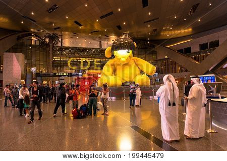 DOHA QATAR - FEBRUARY 27 2016: People at the main hall of Hamad International Airport in Doha Qatar.