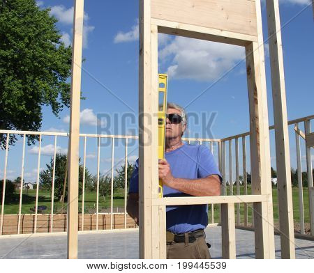 Carpenter reading a level while building a frame for a house