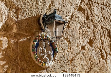 Virgin Mary and a child. Icon under a lantern on a texture wall of a house at the mediterranean island Malta.