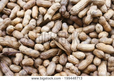 Peanuts in shell texture background. Raw peanuts on display at a farmer's market.