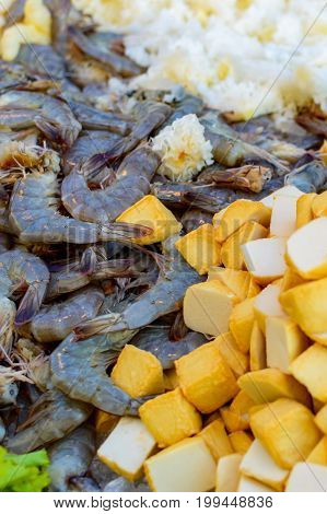 Many Dark Black Or Green King Size Shrimps With Pieces Of Fruits