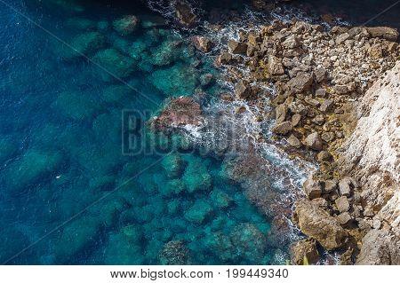 Rocky shore with azure waves, majestic nature landmark of Malta island