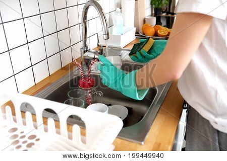 Woman's hands washing the dishes, cleaning home.