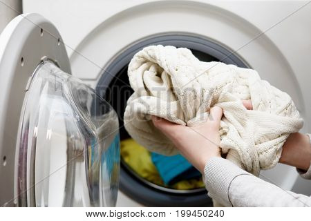 Young woman is prepering clothes for washing.