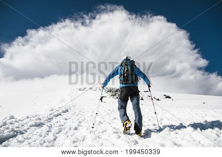 Mountaineer rises uphill to meet a mountain storm coming from the mountain on caucasus