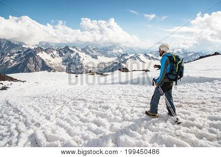 Tired traveler in sunglasses and with a backpack on which the ice-ax is weighing down down from a snowy peak against the background of snow-capped mountains and holding a stick for Scandinavian walking.