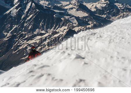The climber climbs the snow-covered summit Against the background of the Caucasian snow-capped mountains . The concept of overcoming difficulties and achieving the goal