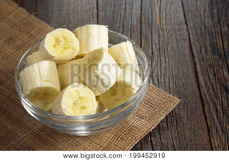 Bananas sliced in glass bowl on dark wooden table
