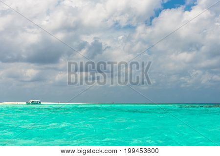 MAAFUSHI MALDIVES - FEBRUARY 29 2016: Horizontal picture of local boat stopped during island hopping at sandbank in Maafushi Maldives.