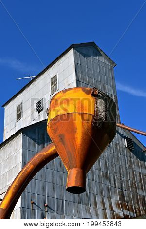 An old grain elevator with a rusty funnel for unloading ground feed or various grains.