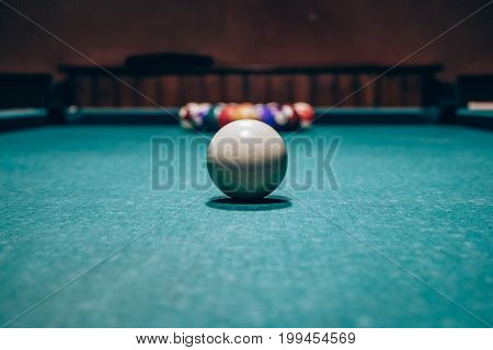 Balls on the table for pool or pocket billiards in a restaurant or bar. Focus on white ball