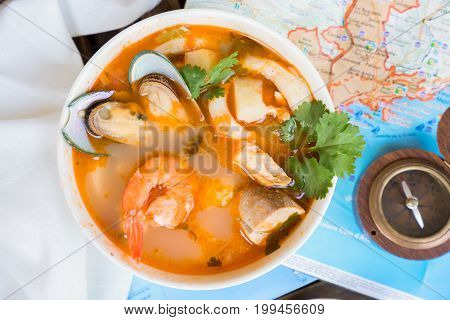 Bowl of Bouillabaisse french seafood soup with compass and mediterranean sea maps