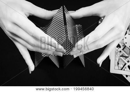 Woman hands assembling house of cards. Black and white photo. Gambling casino fortune and chance theme