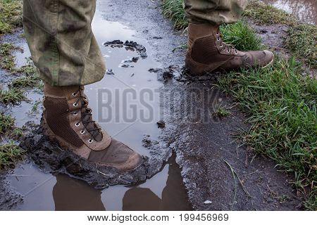 close up army boots in dirt water, soldier walk in fields after rain