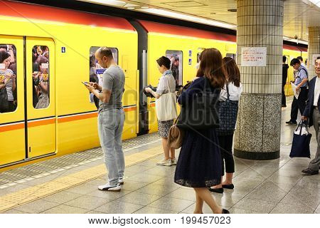 Tokyo, Japan - August 10, 2016: Passengers traveling by Tokyo metro. Business people commuting to work by public transport in rush hour. In Tokyo, Japan