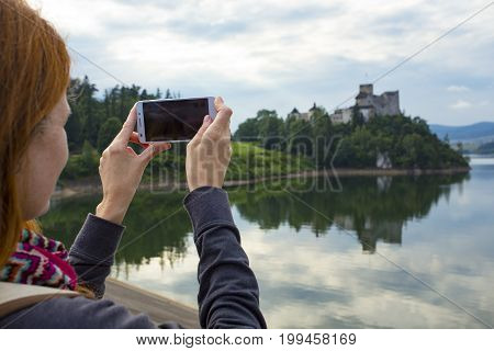 Girl Taking A Picture Of A Beautiful Castle On A Lake Shore