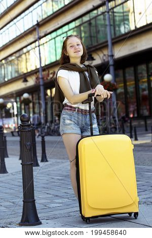 happy smiling girl traveler and her yellow suitcase