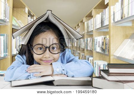 Image of adorable girl studying with book in the library while sitting with a book over her head