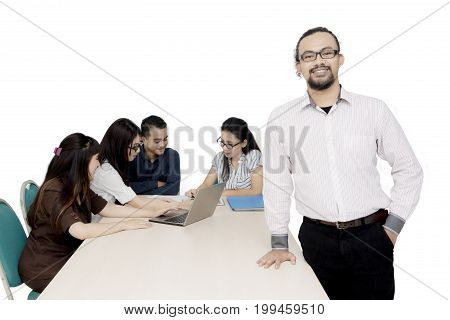 Portrait of a successful African businessman standing in front of his busy team working together