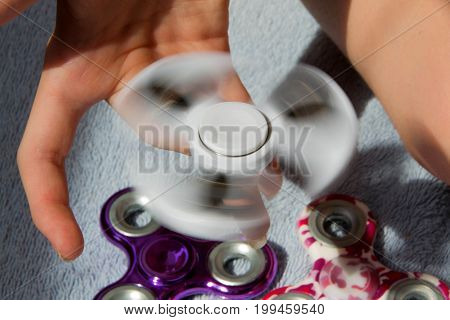 A girl is holding a popular toy fidget spinner. Girl playing with a fidget spinner.