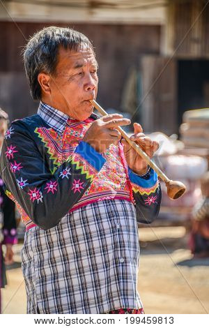 CHIANGMAI THAILAND - JANUARY 25 2015: Hill tribe senior man blowing traditional pipe music equipment in parade of 22nd Traditional Skirt Fabric and The Indigenous Product and Culture Festival in Mae Chaem Chiangmai Thailand