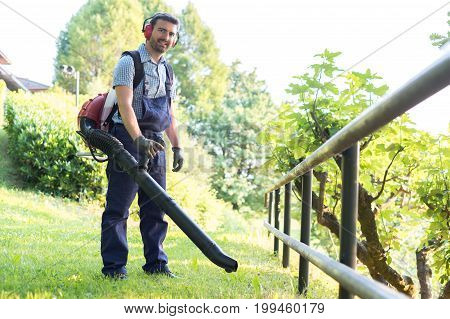 Gardener Clearing Up The Leaves Using A Leaf Blower