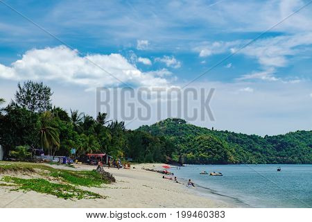 Langkawi, Malaysia - February 14, 2016: Summer vacation on the Pantai Tengah Beach, Langkawi, Malaysia. Unidentified tourists relax on paradise beach sunbathe and swim