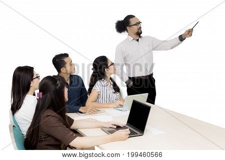 Young Afro businessman presenting something to his team in a business meeting isolated on white background