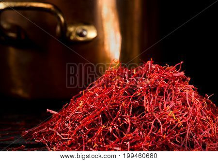 Heap of saffron threads with copper pot and dark background close-up