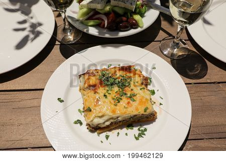 Traditional moussaka with eggplants, ground beef and potatoes in greek tavern. Horizontal. Daylight.